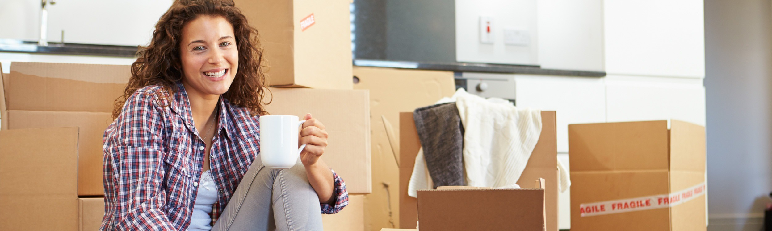 sitting girl holding coffe cup with moving boxes
