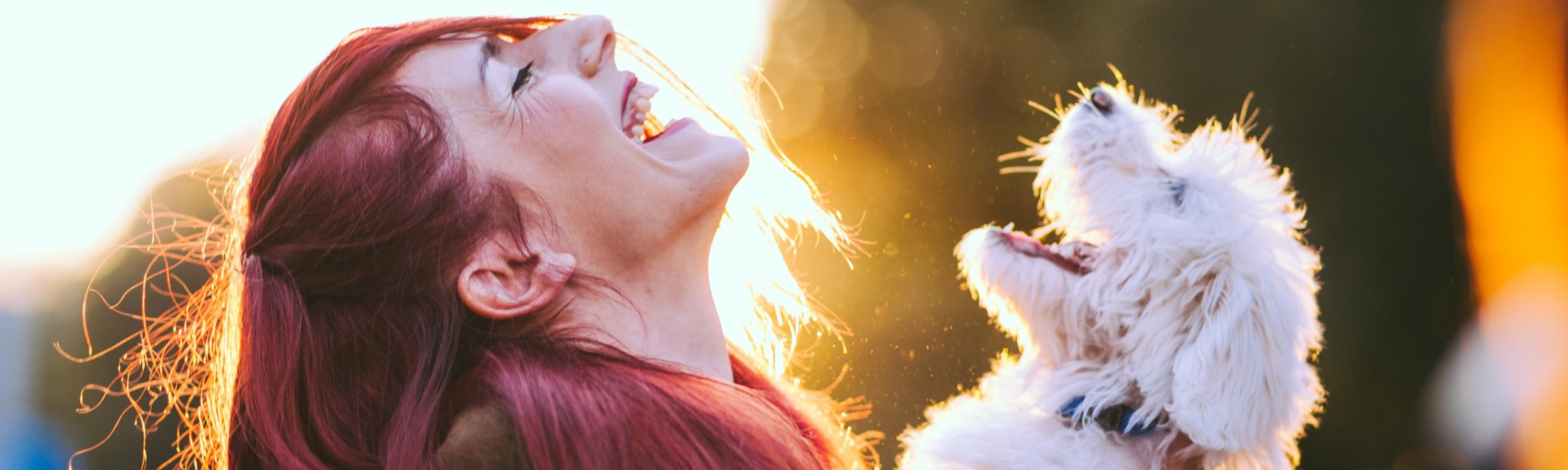 girl with red hair smiling while holding white small dog