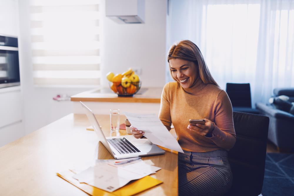 woman smiling sitting in kitchen at laptop reading a bill with phone in hand