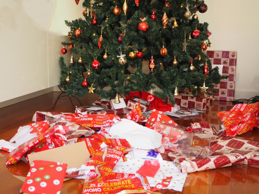 pile of torn up wrapping paper by Christmas tree